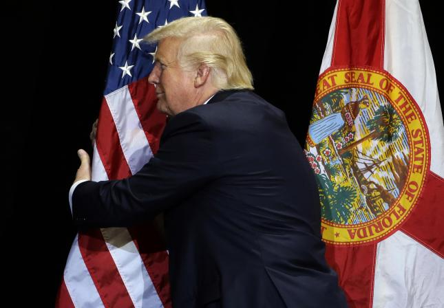 Republican presidential candidate Donald Trump pauses during his campaign speech to hug the American flag Saturday, June 11, 2016, in Tampa, Fla. (AP Photo/Chris O'Meara) ORG XMIT: FLCO107